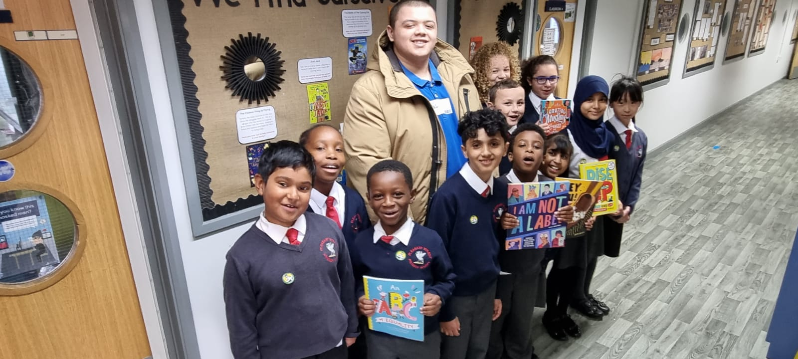 Wade Holligan poses with students from Pleasant Street Primary School. They hold up books from the collection in front of them.